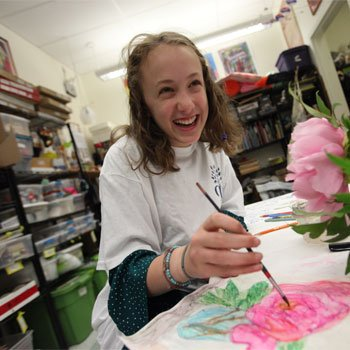 girl laughing while drawing flower - Oak Meadow School, Littleton, MA