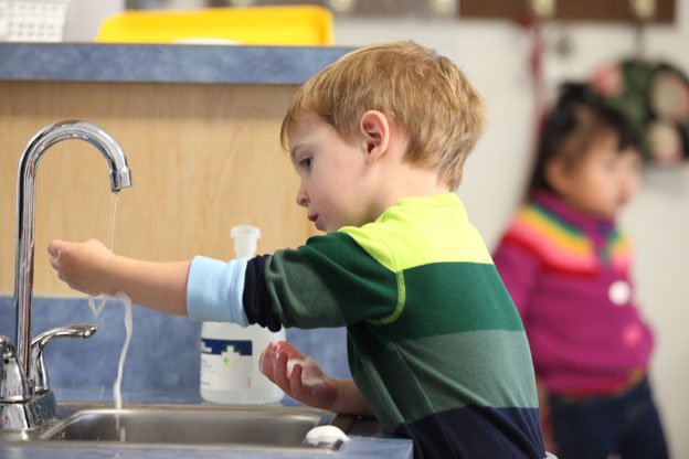 Little boy washing his hands at sink